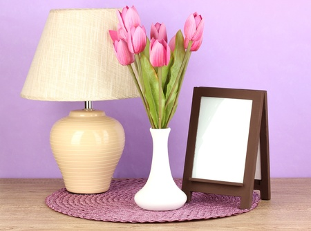 Brown photo frame and lamp on wooden table on lilac wall background Stock Photo - 18039876