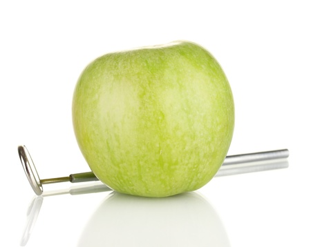 Green apple and dental tool isolated on white photo