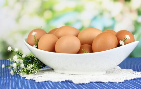 Eggs in white bowl on blue tablecloth close-up Stock Photo - 18042783