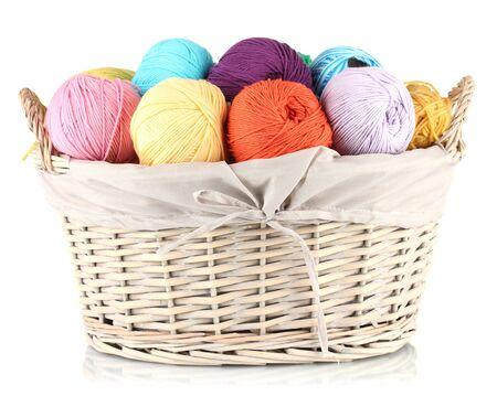 Colorful yarn balls in wicker basket isolated on white photo