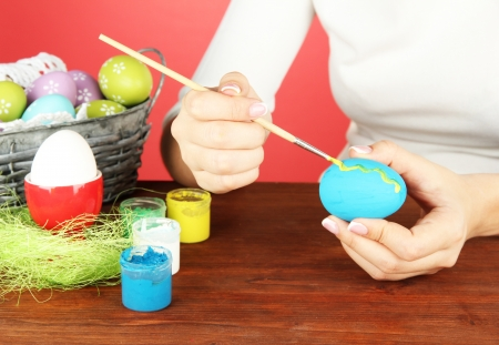 Young woman painting Easter eggs, on color background Stock Photo - 18143803
