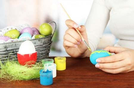 Young woman painting Easter eggs, on bright background Stock Photo - 18143703