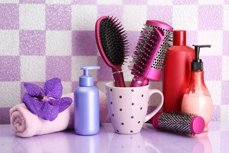 Hair brushes and cosmetic bottles in bathroom  photo