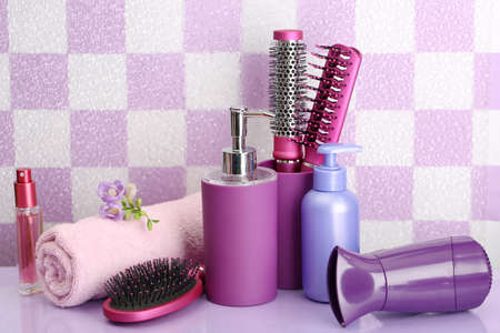 Hair brushes, hairdryer and cosmetic bottles in bathroom  photo