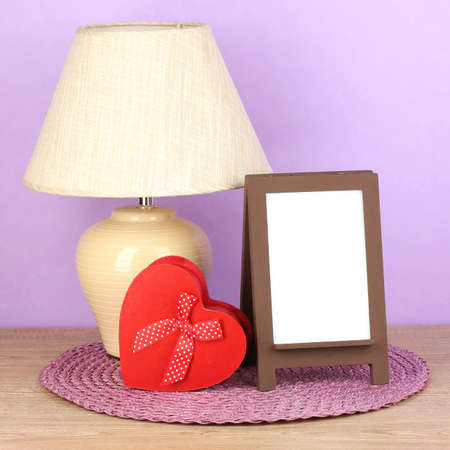 Brown photo frame and lamp on wooden table on lilac wall background Stock Photo - 18144090