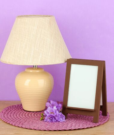 Brown photo frame and lamp on wooden table on lilac wall background Stock Photo - 18143676