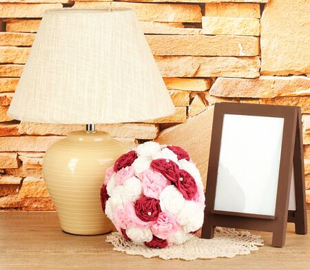 Brown photo frame and lamp on wooden table on stone wall background photo
