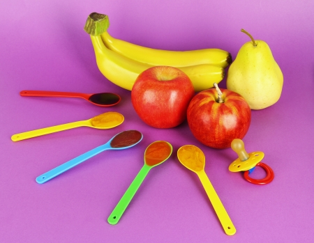 Baby puree in spoons with nipple and fruits on purple background photo