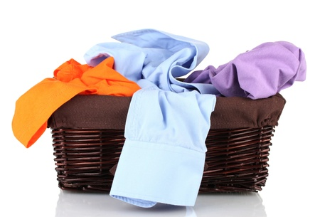 Bright clothes in laundry basket, isolated on white photo