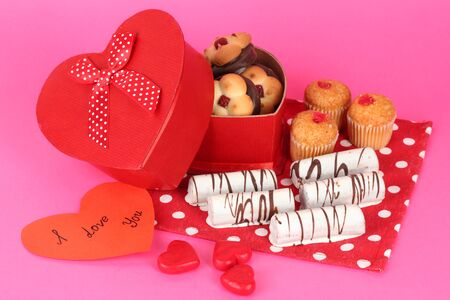 Sweet cookies in gift box on pink background photo
