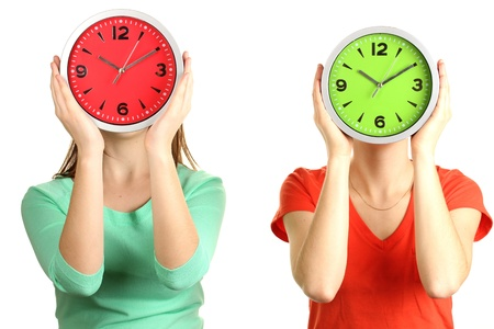 Girls holding clocks over face isolated on white photo