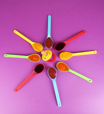 Baby puree in spoons with nipple on purple background photo