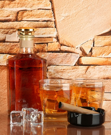 Bottle and Glasses of whiskey and cigar on brick wall background Stock Photo - 18231951