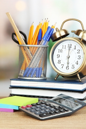 school time: School supplies with clock on wooden table