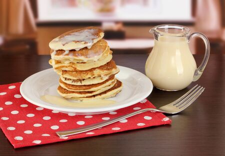 Sweet pancakes on plate with condensed milk on table in room Stock Photo - 18231564