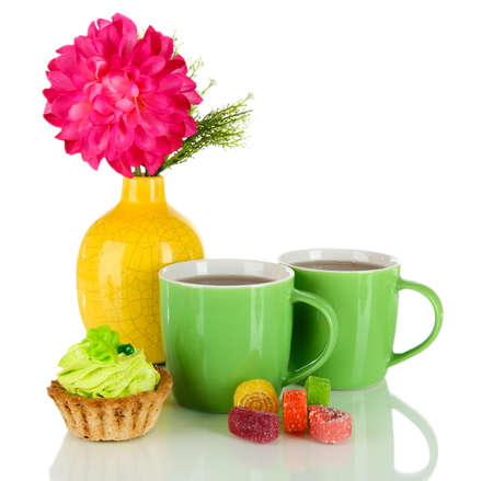 Cups of tea with candy,cake and flower isolated on white photo