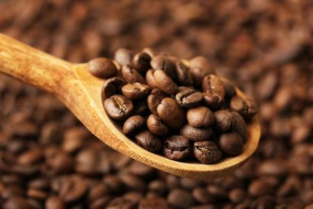 cafe colombiano: Granos de café en cuchara de madera, de cerca Foto de archivo