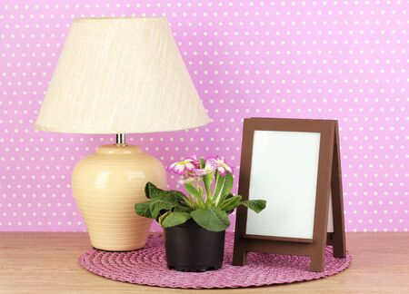 Brown photo frame and lamp on wooden table on lilac wall background Stock Photo - 18231846