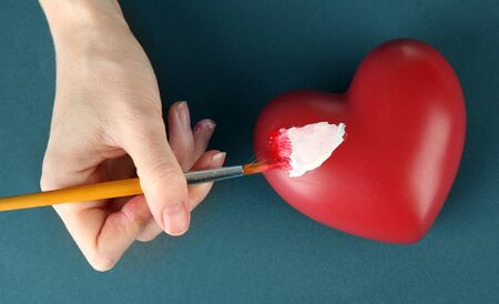 Hand paints white spot on heart, on color background. Conceptual photo treatment of heart disease. photo