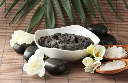Composition with cosmetic clay for spa treatments, on bamboo background photo