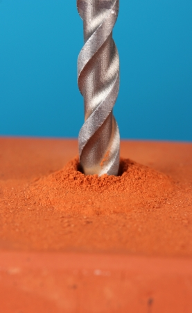 Close-up image of drilling hole on brick, on color background photo