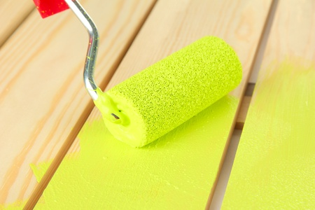 modernise: Paint roller brush with green paint, on wooden background