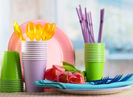 Multicolored plastic tableware on table with tulips close up photo