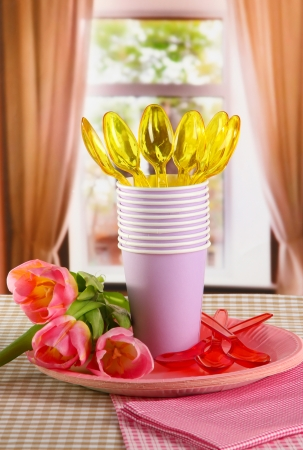 Multicolored plastic tableware on window background photo