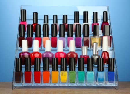 Bright nail polishes on shelf on blue background photo