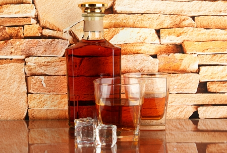 Bottle and Glasses of whiskey and ice on brick wall background photo