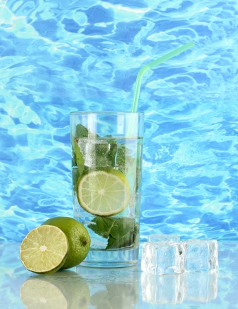 Glass of water with ice, mint and lime on sea background photo