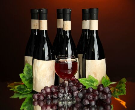 Composition of wine bottles, glass and  grape, on dark red background Stock Photo - 18294846