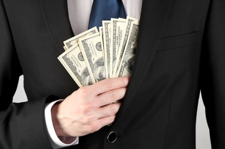 Business man hiding money in pocket on grey background Stock Photo - 18295130