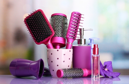 Hair brushes, hairdryer and cosmetic bottles in beauty salon  photo