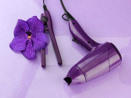 Hair dryer and straighteners  on purple background Stock Photo - 18295096