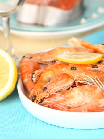 Shrimps with lemon on plate on wooden table close-up photo