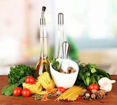 Composition of mortar, pasta and green herbals, on bright background photo