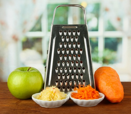Metal grater and apple, carrot, on bright background photo