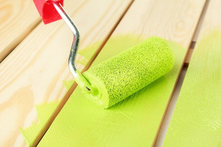 Paint roller brush with green paint, on wooden background
