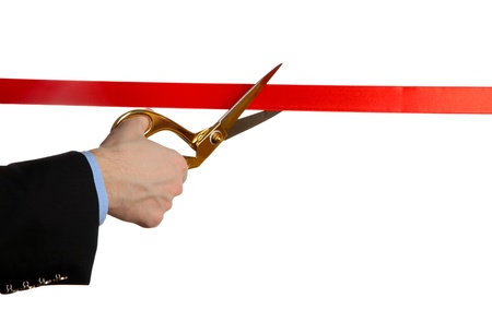 ribbon cutting: Mans hand cutting red ribbon with pair of scissors isolated on white Stock Photo