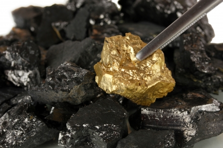 tough luck: Tweezers holding golden nugget on coals background close-up