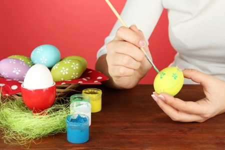 Young woman painting Easter eggs, on color background Stock Photo - 18325496
