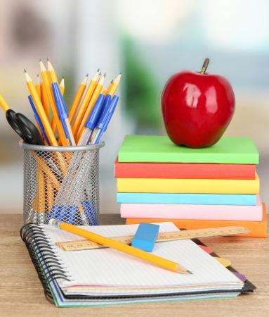 Schulbedarf mit Apfel auf Holztisch Standard-Bild