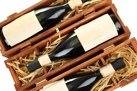 Bottles of old red wine in gift wooden box, isolated on white photo