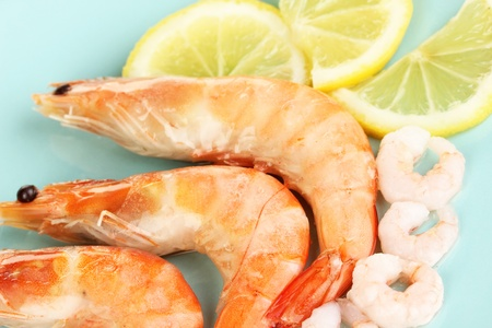 Shrimps with lemon on plate close-up photo