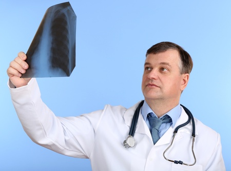 Medical doctor analysing x-ray image  on blue background Stock Photo - 21542729