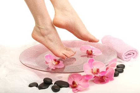 Female feet in spa bowl with water, isolated on white Stock Photo