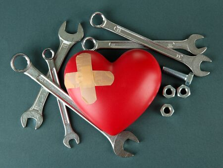 Heart and tools. Concept: Renovation of heart. On color background photo