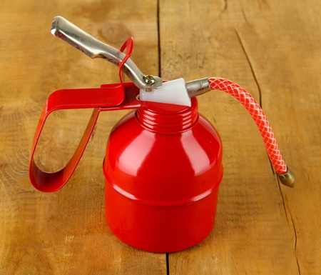 Red oil can, on wooden background Stock Photo - 18325111