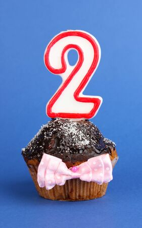 Birthday cupcake with chocolate frosting on blue background Stock Photo - 18325416